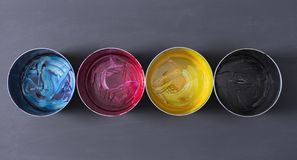 Top view of old CMYK paint cans on dark background. Colorful background. royalty free stock photos