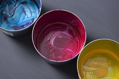 Top view of old CMYK paint cans on dark background. Colorful background. royalty free stock photography