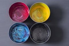 Top view of old CMYK paint cans on dark background. Colorful background. royalty free stock photo
