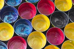 Top view of old CMYK paint cans on dark background. Colorful bac. Kground royalty free stock photography