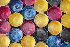 Top view of old CMYK paint cans on dark background. Colorful bac royalty free stock image