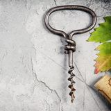 Top view of an old cork screw and grape leaf on gray concrete ba Royalty Free Stock Photos
