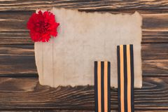 Top view of old empty paper, carnation and st. george ribbons on wooden surface royalty free stock photos