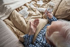 Senior male taking medicine at home. Top view of old man sitting in bed and holding pills and glass of water. He is ill and treating himself Stock Photography