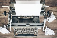 Top view of old manual typewriter and crumpled sheets of paper on rustic wooden desk stock photo