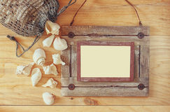 Top view of old nautical wooden frame and natural seashells on wooden table Royalty Free Stock Image