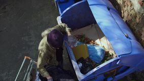 Top view of old tramp collecting empty packings from trash can. Old homeless man looking for food and other stuff in garbage stock footage