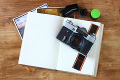 Top view of old vintage camera and pictures over wooden brown background. Royalty Free Stock Photos