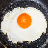 Top view of one fried egg in black frypan Royalty Free Stock Photography