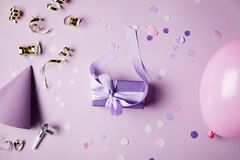 Top view of one violet present box, balloon, party hat and confetti pieces on surface royalty free stock image