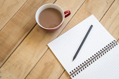 Top view of open book and coffee cup on wooden table. Background Stock Image