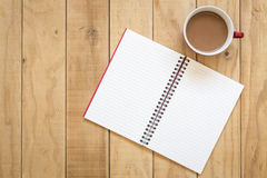Top view of open book and coffee cup on wooden table. Background Stock Photos