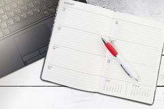 Open calendar or planner and pen on laptop computer. Top view of open calendar or planner and pen on laptop computer stock photography