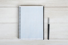 Top view of an open empty notebook and black pen on light wooden surface Stock Photography