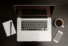 Top view of the open laptop, notebook with pen, smart phone and a mug of coffee on a black wooden table Royalty Free Stock Photos