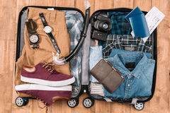 Top view of open luggage full of men clothes, gadgets, and other essential vacation items Royalty Free Stock Images