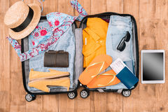 Top view of open luggage full of woman`s clothes and other essential vacation items Stock Images
