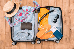 Top view of open luggage full of woman`s clothes and other essential vacation items Stock Photography