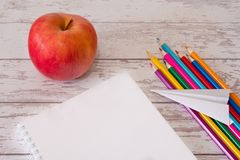 Top view of the open note pad with copyspace and colorful pencils with paper airplane and red apple on a wooden desk. Concept of royalty free stock images