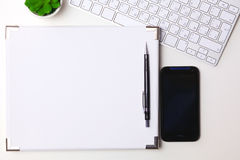 Top view open notebook, pencil and plant potted on white desk background Stock Image