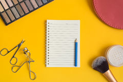 Top view of an open  notepad and blue pencil surrounded by cosme Stock Photos