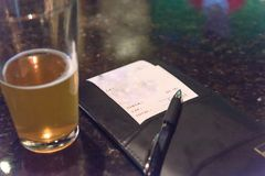 Pint glass beer and leather bill holder with restaurant check. Top view open pint glass beer next to leather bill holder with restaurant check and pen. Close-up stock photography