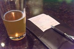 Pint glass beer and leather bill holder with restaurant check. Top view open pint glass beer next to leather bill holder with restaurant check and pen. Close-up stock image