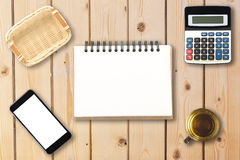 Top view of open spiral blank notebook with smartphone, calculat stock images