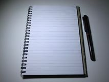 Top view of open spiral blank notebook. On white desk background The shadow of the lamp. Overtime Stock Photography
