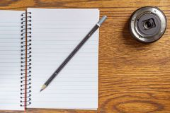 Top view of open spiral notebook with black pencil and camera lens on desk background. Top view of open spiral notebook with black pencil and camera lens on Stock Photos
