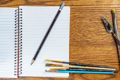 Top view of open spiral notebook with black pencil and paint brushes on desk background. Top view of open spiral notebook with black pencil and paint brushes on Royalty Free Stock Image