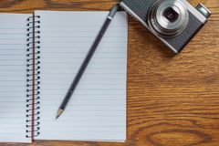 Top view of open spiral notebook with black pencil and photo camera on desk background. Top view of open spiral notebook with black pencil and photo camera on Stock Photo