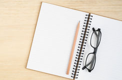 Top view of open spiral notebook with brown pencil and black eye Stock Images