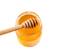 Top of view of opened honey jar on white background with wooden honey dipper on top Royalty Free Stock Images