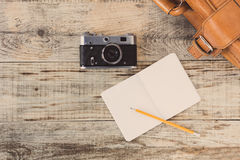 Top view on opened notebook, old, vinage camera and suitcase on wooden office desk, old planks. Hipster style Royalty Free Stock Photography