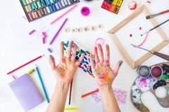 Top view opened painted female hands over Create word lettering with many colorful paintiing materials on white background. Create. Your life, be cheerful stock image
