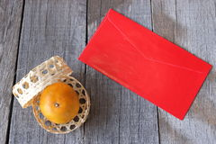 Top view of orange in a basket on old wooden board with Chinese red envelope packet or ang pao background. Happy Chinese new year Stock Photo