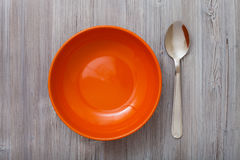 Top view orange bowl and spoon on gray brown table Royalty Free Stock Image