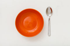 Top view of orange bowl and spoon on white plaster Stock Photography