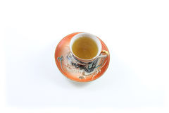 Top view of orange and white Japanese dragon teacup and saucer with tea Stock Photos