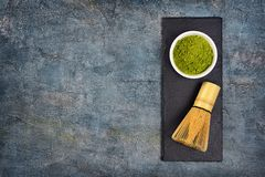 Top view on organic green matcha tea�powder with bamboo whisk on black slate board. Top view on organic green matcha tea�powder in white bowl with royalty free stock images