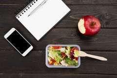 Top view of organic salad with apple, notebook and smartphone Royalty Free Stock Image