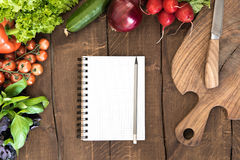 Top view of organic vegetables, chopping board and blank notepad with pencil. On wooden background Royalty Free Stock Photography