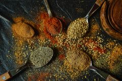 Top view on oriental spices in spoons and scattered on the black metallic tray in Asian style stock images