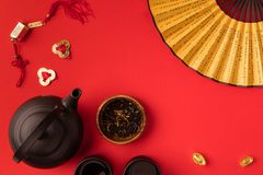 Oriental decorations and tea set. Top view of oriental tea set, decorations and fan with characters isolated on red Royalty Free Stock Photo