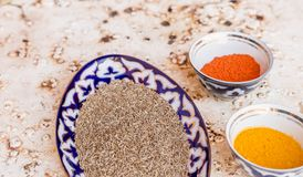 Composed bowls with various spices. Top view of ornamental bowls filled with different spices and condiments on solid surface royalty free stock photos