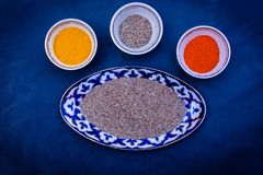 Composed bowls with various spices. Top view of ornamental bowls filled with different spices and condiments on solid surface royalty free stock photography