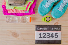 Top view of outfit for runner on wooden background. Bib number,  bottle of water, gps watch, running shoes, running waist bag, shorts, shirt, and sport bra Royalty Free Stock Photos