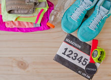 Top view of outfit for runner on wooden background. Bib number, finisher medal, bottle of water, gps watch, running shoes, running waist bag, shorts, shirt Stock Photos