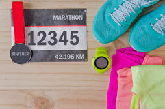 Top view of outfit for runner on wooden background. Bib number, finisher medal, bottle of water, gps watch, running shoes,  shorts, shirt, and sport bra Stock Photography